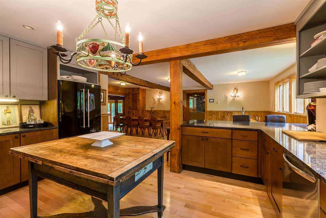 The highlight of this Rustic-style kitchen is the decorative small chandelier hanging from the white ceiling that has depictions of winged dragons in its design. This casts a warm yellow light on the wooden table in the middle of the hardwood flooring that serves as a kitchen island.
