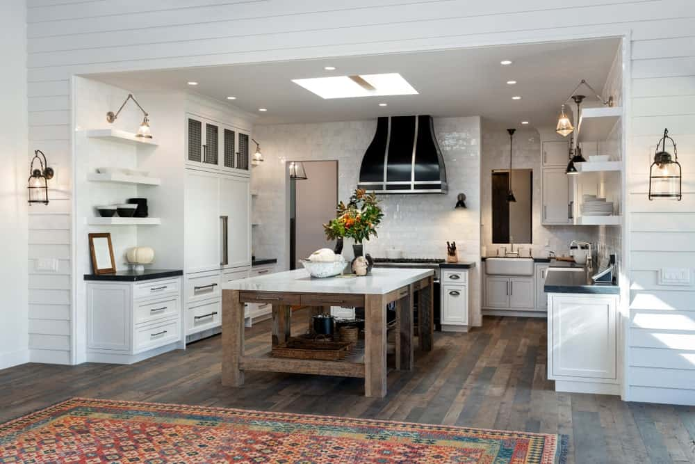 This Rustic-style kitchen is predominantly white with white shaker cabinets and drawers, white walls and a white ceiling brightened by the sky light. This is then contrasted by the wooden frame of the large kitchen island that blends with the hardwood flooring.