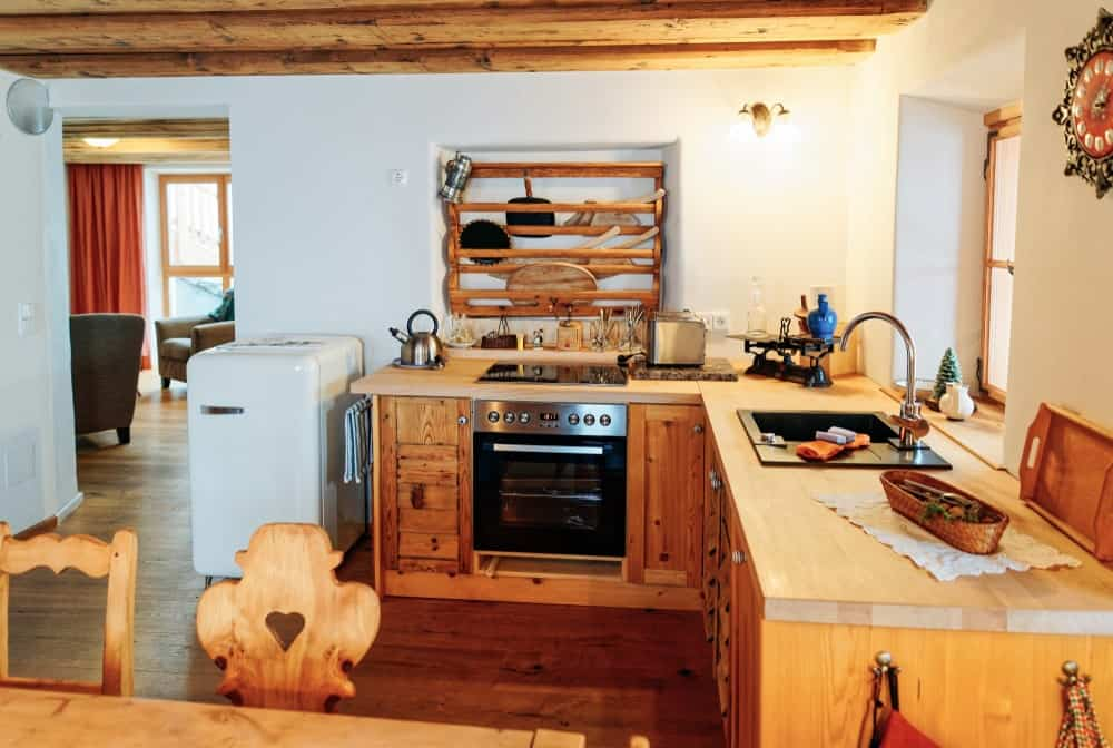 The Rustic-style wooden L-shaped peninsula that has wooden countertops is augmented by the modern appliances and sink that it houses within its wooden cabinets and drawers. This peninsula matches with the hardwood flooring as well as the exposed wooden beams of the ceiling.