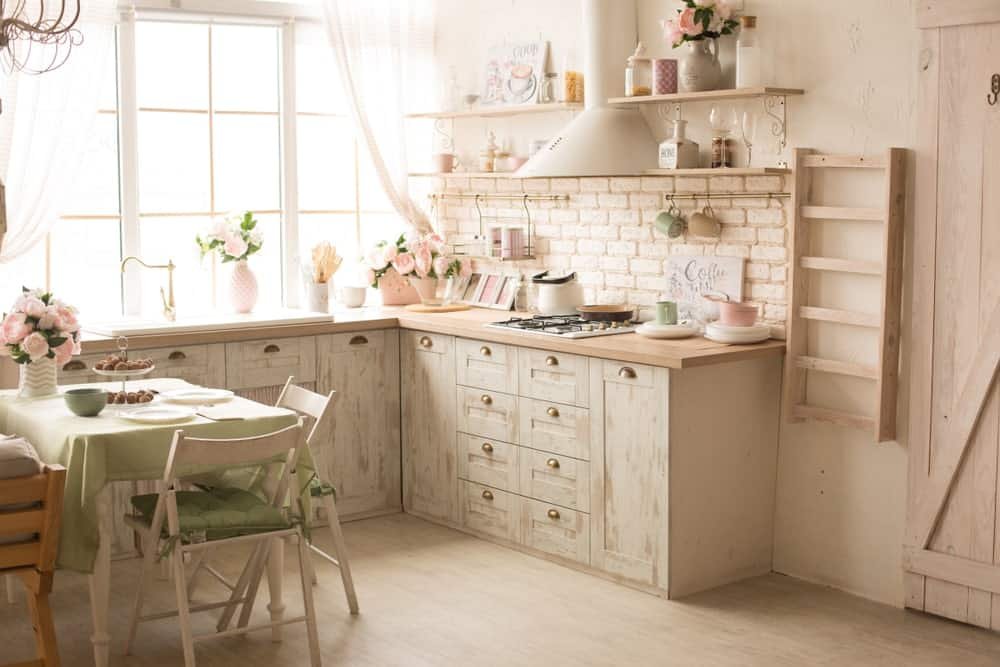 This bright and fresh chic kitchen has a Rustic-style quality to its distressed wooden cabinets that matches with the light pink brick wall and the light hardwood flooring. These are all further lightened by the natural lights coming in from the curtained window by the sink area.
