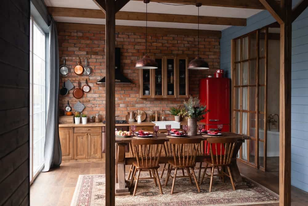 The wooden kitchen peninsula that has a wooden countertop is paired with a red brick wall that has wall-mounted hooks for the pans and a few floating cabinets. These are a nice complement to the bright red fridge placed in the corner.