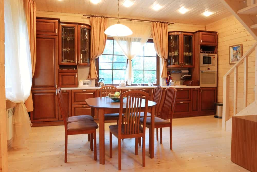 This Rustic-style kitchen shares its light hardwood flooring and wooden ceiling with an informal dining area that has a wooden dining set in a dark brown hue that matches with the shaker cabinets and drawers of the kitchen peninsula augmented by warm yellow lights.