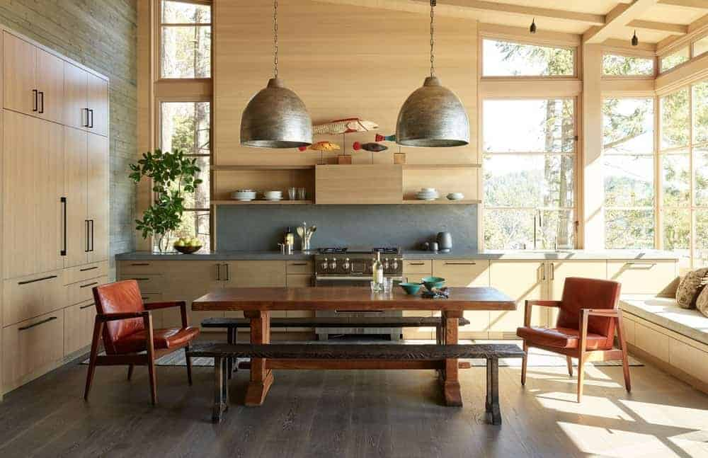 This is a Rustic-style kitchen, dining area and reading nook all in one room that has a high wooden shed ceiling with exposed wooden beams. This blends with the wooden peninsula and cabinets of the kitchen illuminated by the bright windows.