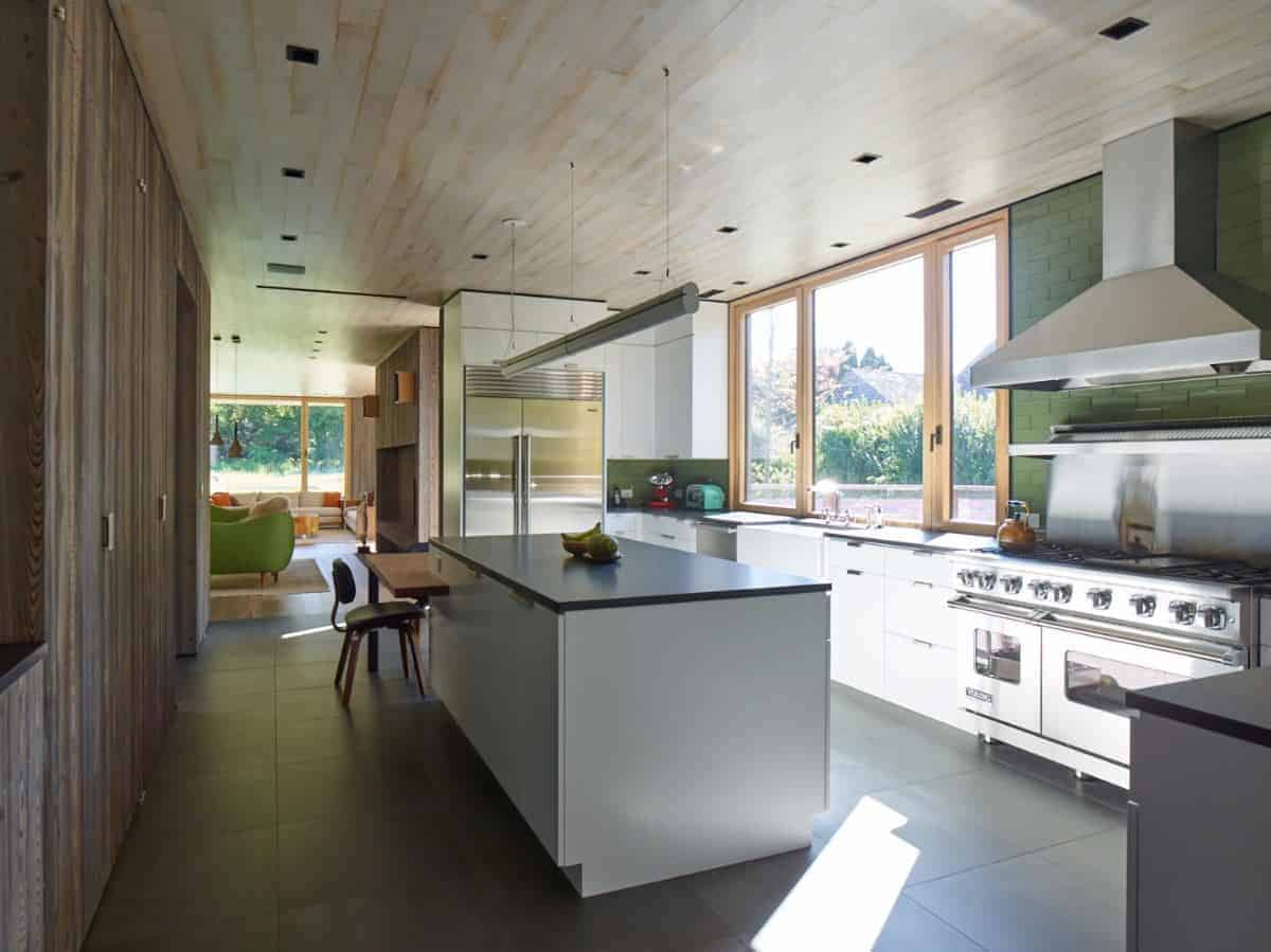 The distressed white wooden ceiling has a plank finish that matches with the frame of the windows above the sink area of the L-shaped kitchen island that houses the stainless steel appliances complemented by the dark gray flooring tiles.