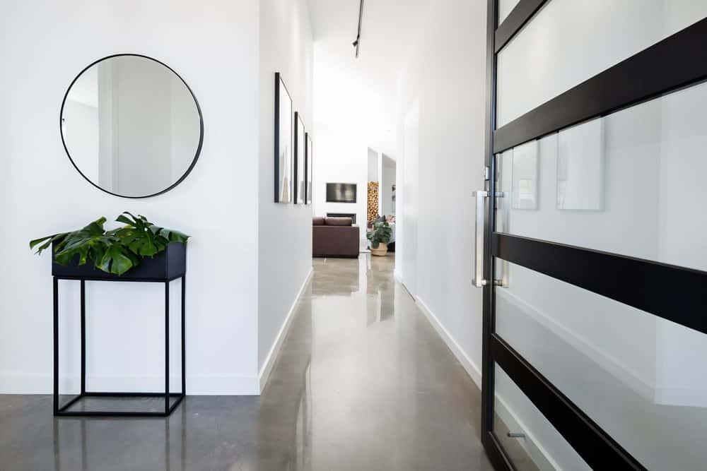 This Scandinavian-style foyer has beauty in its simplicity. It has a gray concrete flooring that goes well with the dark planter on a wrought iron pedestal as well as the black frames of the main door that alternates with the glass panels. These are all brightened by the white walls and ceiling.