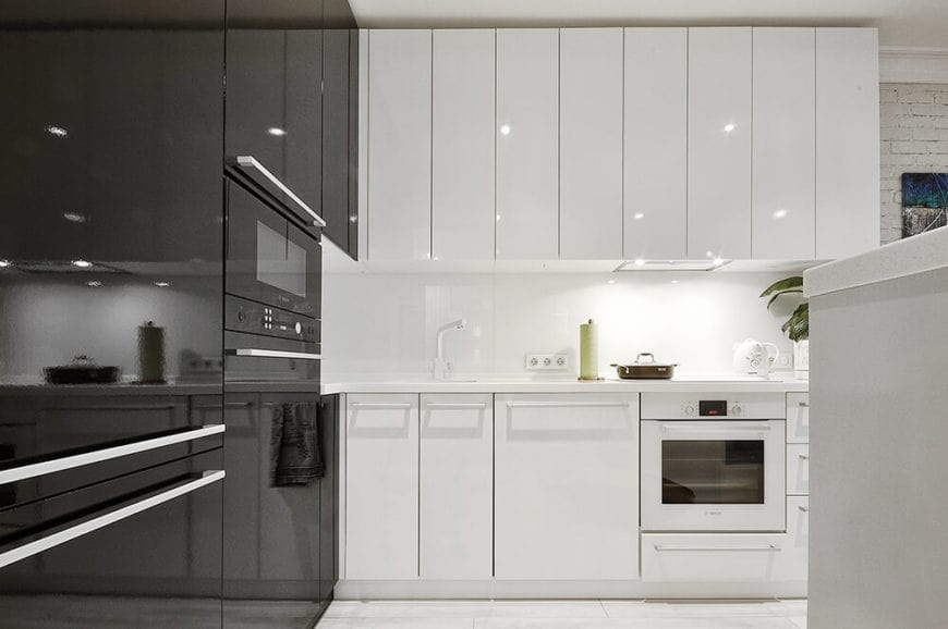 This kitchen looks like it came straight out of a science fiction movie about the future. The sleek and modern appliances contrast each other with their black and white hues that blend with the built-in cabinets and drawers surrounding them.