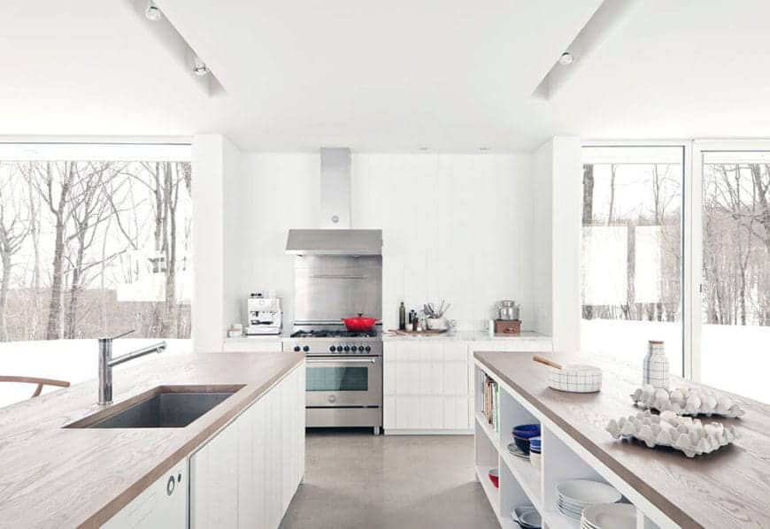 The white ceiling, white walls, and white built-in cabinets and drawers are contrasted by the wooden countertops of the two islands. The brightness of the room is augmented by the doors flanking the cooking area and its modern metallic oven stove.