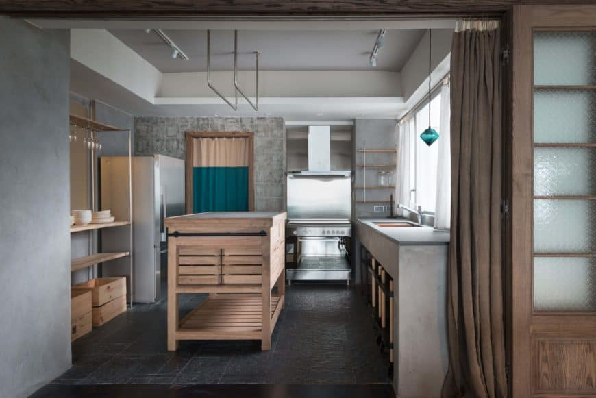 The dark flooring and tray ceiling of this Scandinavian-Style kitchen may be small but it was maximized by the efficient use of space. There is a small wooden kitchen island in the middle that is surrounded by modern appliances against the walls as well as a kitchen peninsula.