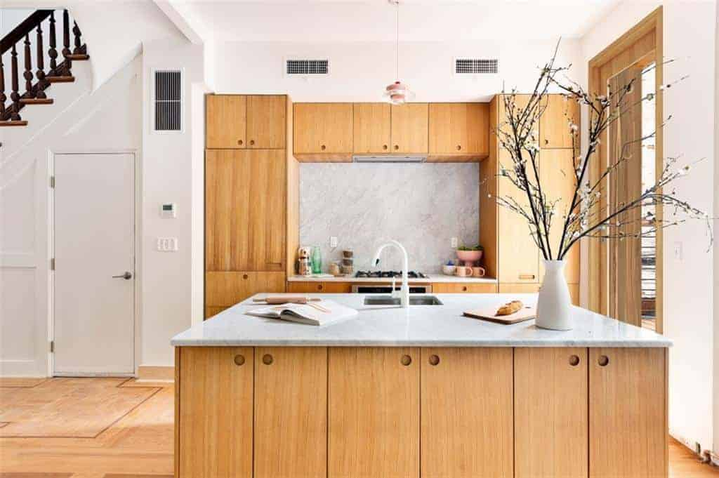 This kitchen has a large wooden structure against the far wall that houses the cooking area and has built-in cabinets and drawers for storage. This design is mirrored in the kitchen island that has a white countertop. There are no cabinet and drawer handles, but holes carved into the wood for a nice effect.