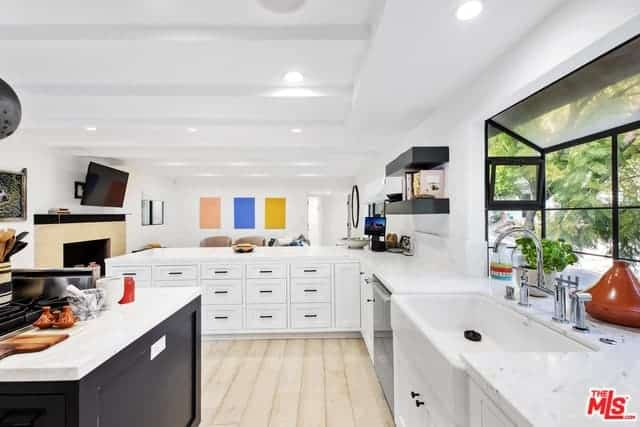 The bright white tray ceiling has exposed beams that mirror the countertops of the L-shaped peninsula and kitchen island. The sink area is facing a glass window that offers a lovely scenery. The kitchen island is made of dark wood that contrasts the light-hued flooring.