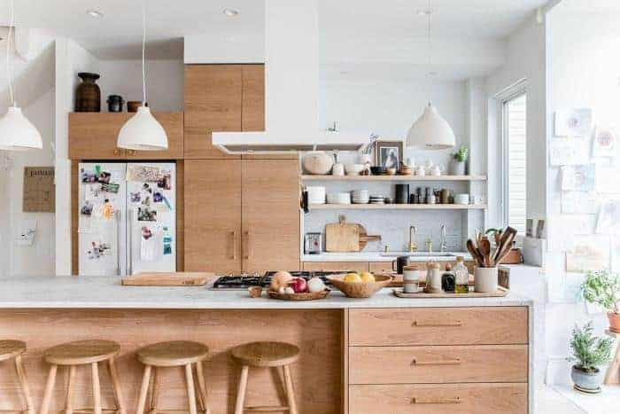 The bare wooden tones stand out against the bright ceiling and walls of this kitchen. The white fridge is housed by a wooden structure that extends to the ceiling and sink area that is topped with open shelves. The central kitchen island has a white countertop with built-in wooden drawers.