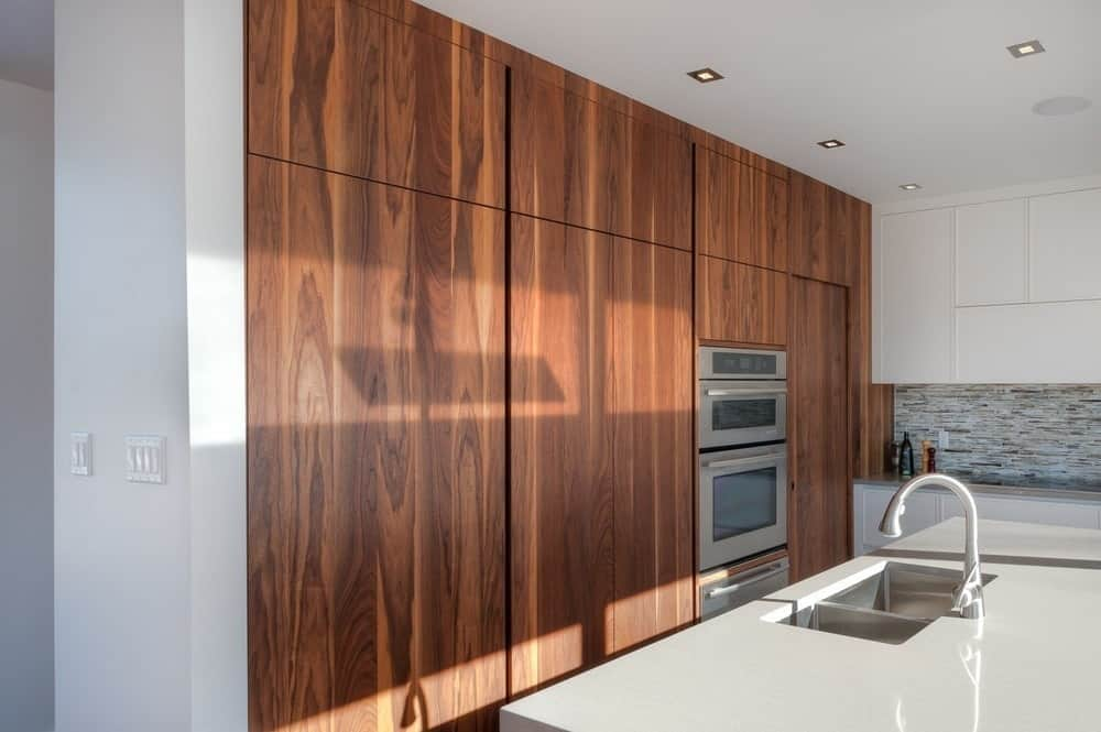 This kitchen has a simple design that emphasizes its straight lines and sleek monochromatism. The sleek white countertop of the kitchen island houses the sink area and matches the white cabinets and drawers. This is contrasted by the wooden finish of the wall that houses the oven.