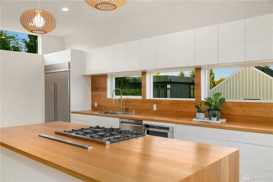This Scandinavian-Style kitchen did a reversal of the usual designs of a kitchen. It has a white peninsula and kitchen island with countertops made of polished wood which extends to the backsplash. The modern fridge is embedded in the white walls that extend to the white ceiling that has a pair of pendant lights.