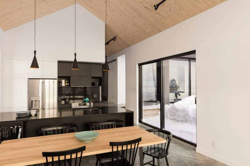 The highlight of this Scandinavian-Style kitchen is its gorgeous black and white theme. The white walls contrasts nicely with the black countertops of the kitchen island and the cooking area that has built-in cabinets and drawers also with a black finish that makes the modern appliances pop out.