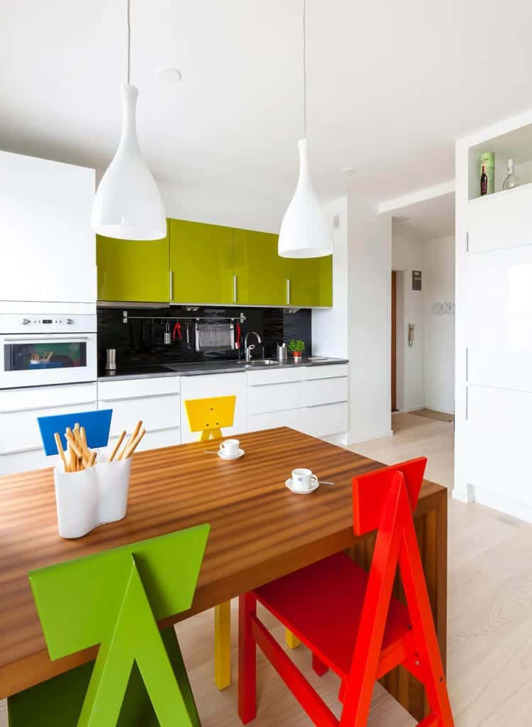 This kitchen shares the hardwood floor, white ceiling and walls with the dining area that has colorful wooden chairs. The hanging cabinets over the cooking area stand out with its avocado color against the white walls and white cabinets of the wooden structure housing the fridge.
