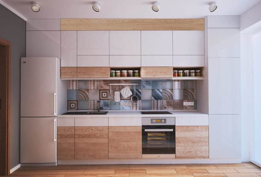 The colorful and random patterned tiles of the backsplash stand out against the simple tones of the rest of this Scandinavian-Style kitchen. There is a wooden flooring that matches the cabinets of the cooking area and spotlights mounted on the white ceiling.