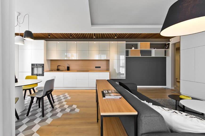 This Scandinavian-Style kitchen is so simple that it only makes up one wall of the large room that also contains the dining area and living room. The ceiling over the kitchen has exposed wooden beams that reflect the hardwood floor. The whole kitchen is one huge wooden structure that has a white sleek finish.