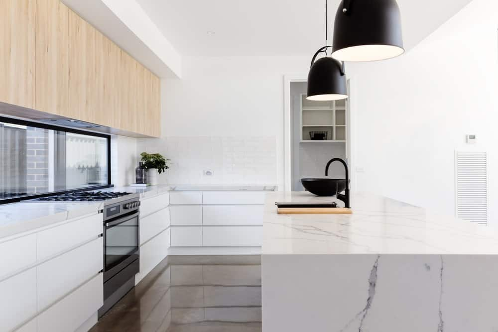 A modish Scandinavian-Style kitchen with sparkling flooring. The center island and the kitchen counters are made topped with marble countertops.