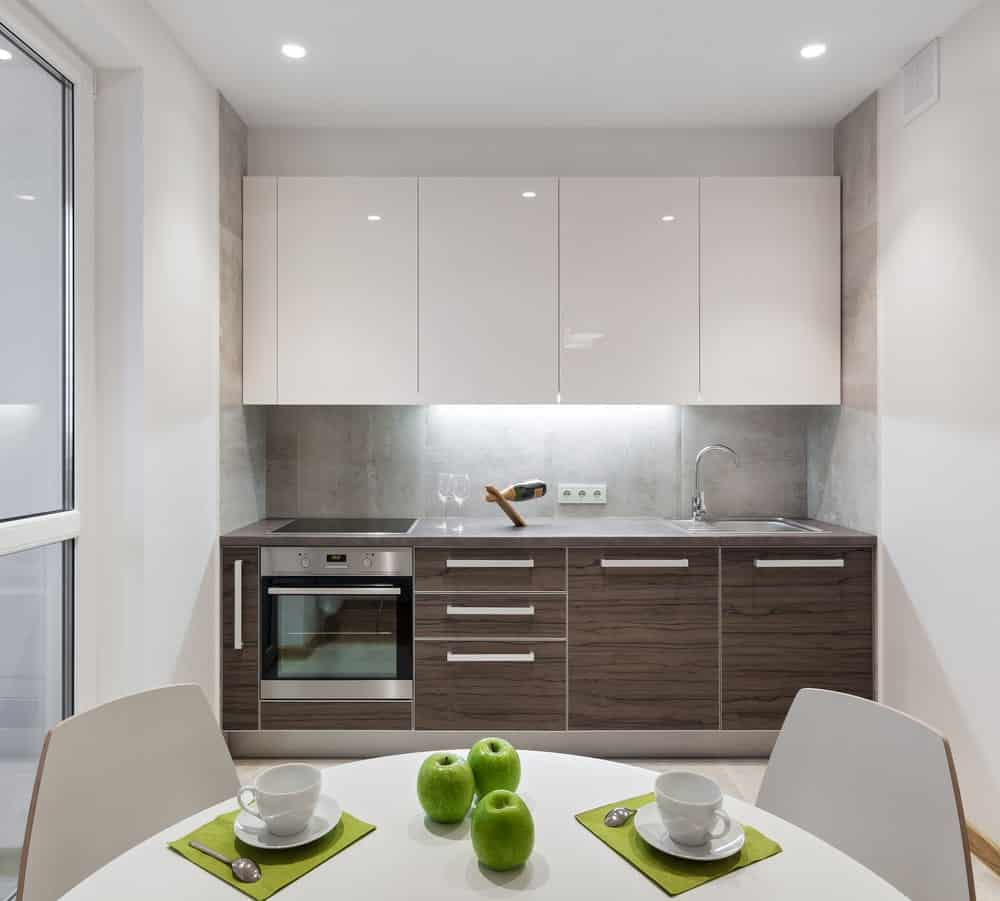 White single wall kitchen featuring a stylish kitchen counter and a small white dining nook.