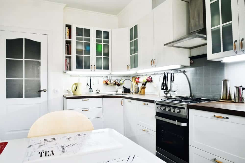 This Scandinavian-Style kitchen boasts white cabinetry, walls and counters with a dark-finished countertop.