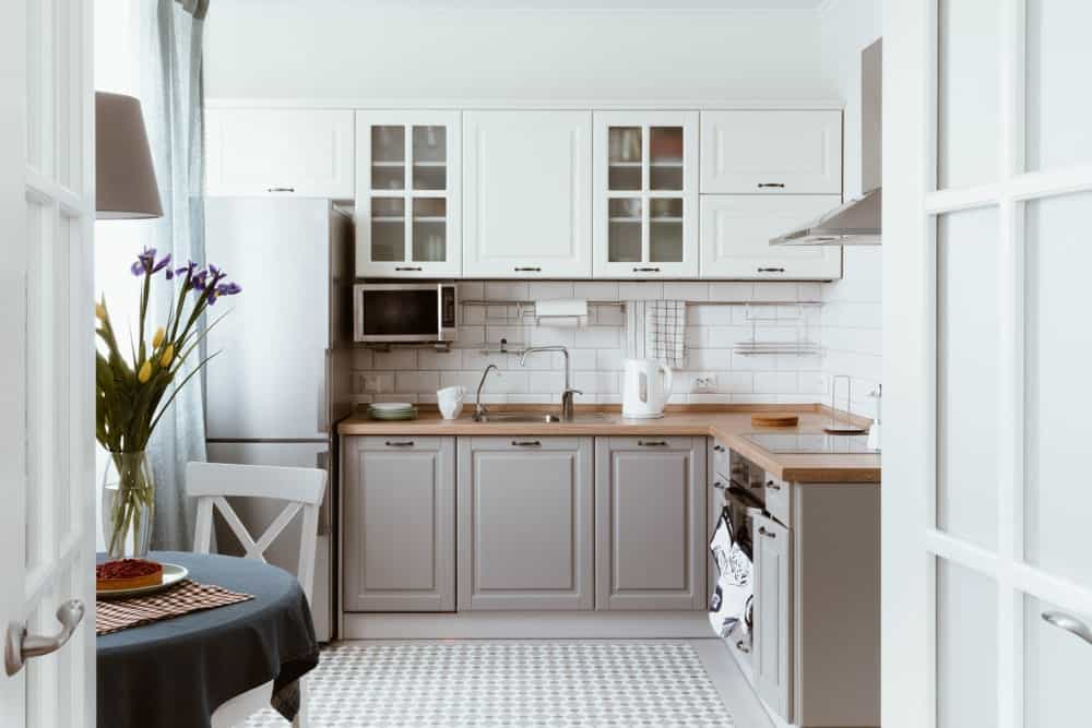 This Scandinavian-Style kitchen offers a hardwood countertop on the kitchen counter. The tiles flooring looks very classy, while the dining table set looks lovely.
