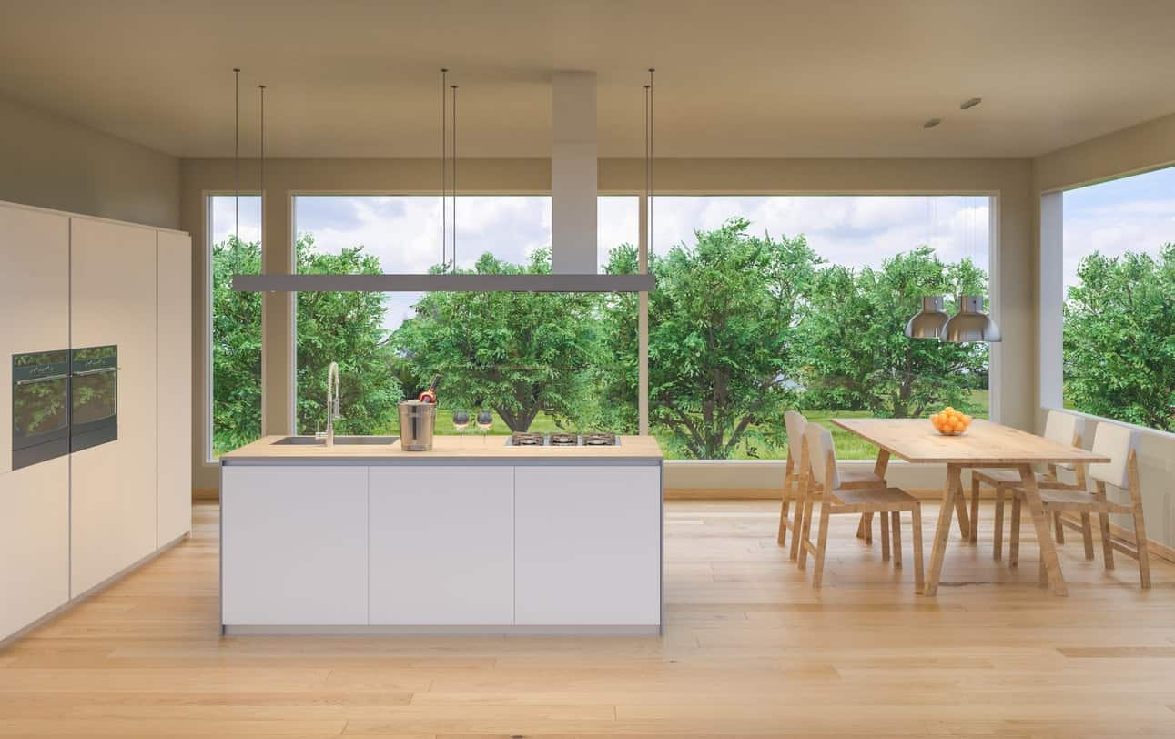 A large Scandinavian kitchen featuring a hardwood flooring matching the dining table set on the corner lighted by a couple of pendant lights.