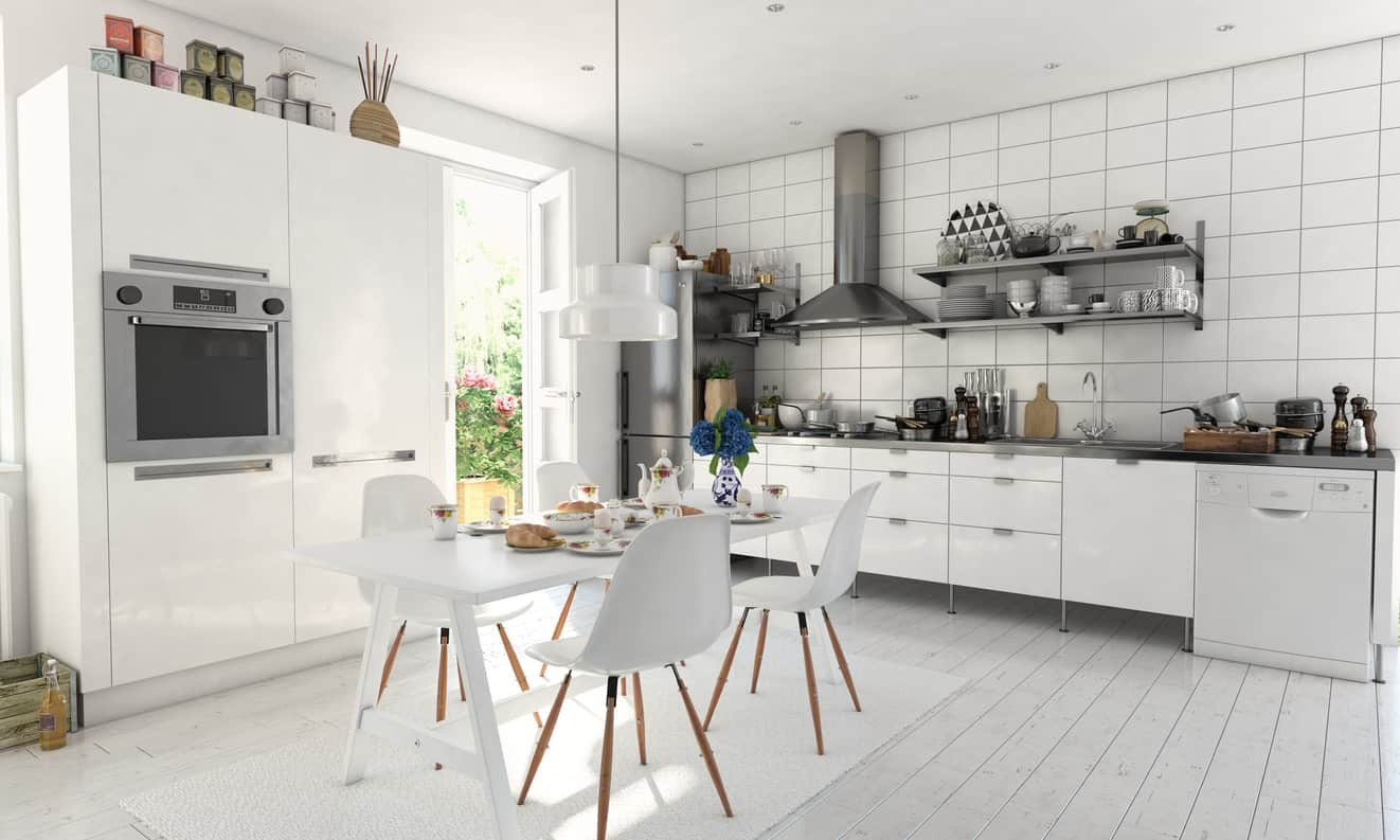 Large Scandinavian kitchen featuring white tiles backsplash wall and a hardwood flooring with white finish. The dining table set for four is also finished in white paint.