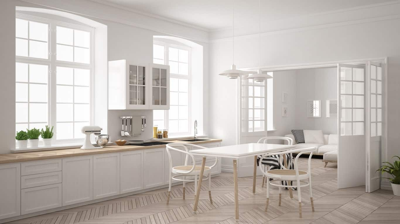 This large Scandinavian kitchen boasts a herringbone style hardwood flooring surrounded by white walls and kitchen counters.