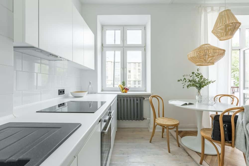 A small Scandinavian kitchen featuring white cabinetry, counters and small table paired with wooden chairs and pendant lights.