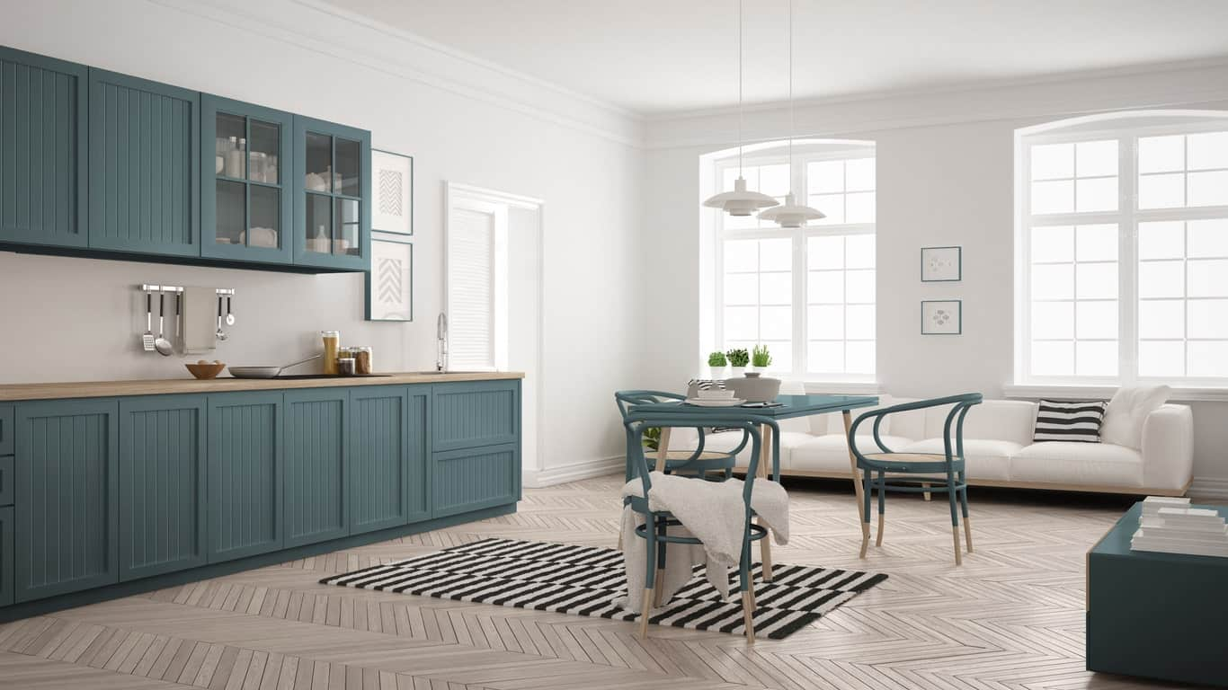 A spacious Scandinavian-Style kitchen boasting a hardwood flooring surrounded by white walls with a green shade. There's a long sofa set on the side near the windows.