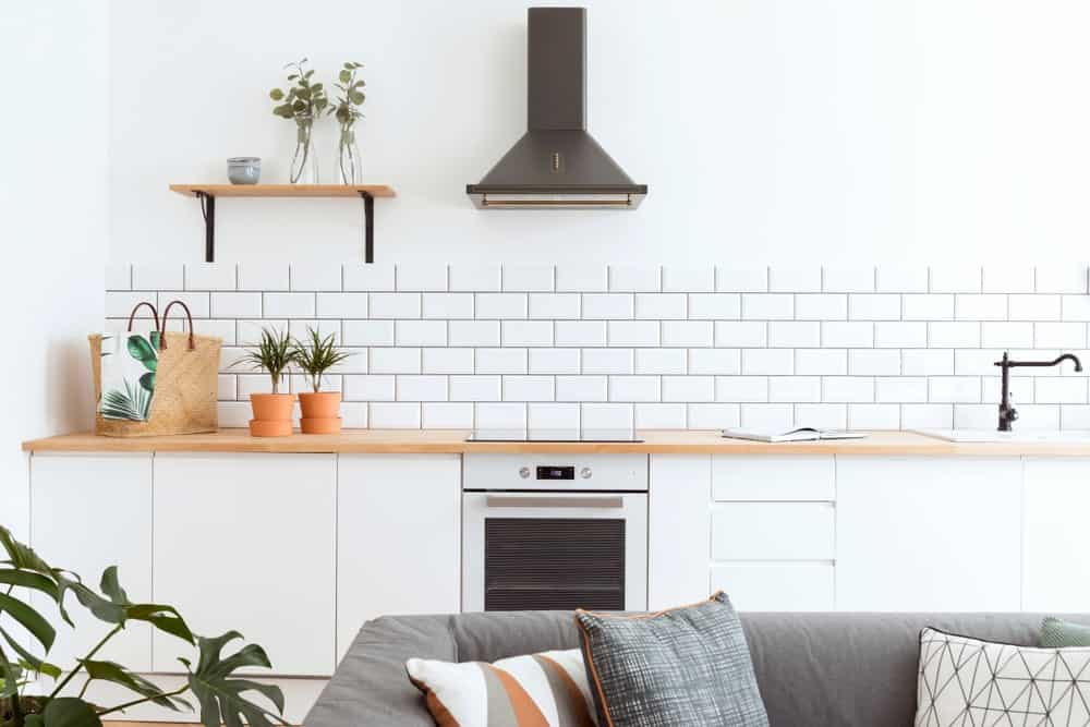 Large Scandinavian kitchen featuring white walls, white tiles backsplash and white kitchen counters with a wooden countertop. There's a sofa set on the middle too.