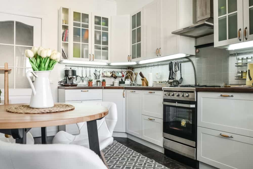 This Scandinavian kitchen style features white cabinetry and white kitchen counters with a wooden countertop. There's a small dining nook on the middle as well.