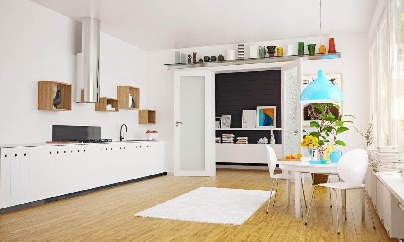 A spacious Scandinavian kitchen featuring a hardwood flooring, white walls matching the long kitchen counter set.