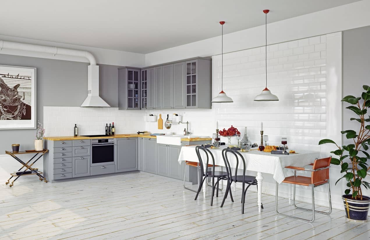 This spacious Scandinavian kitchen features white and gray finish combo. The wall decor looks charming. The dining table looks cute as well, lighted by a pair of pendant lights.