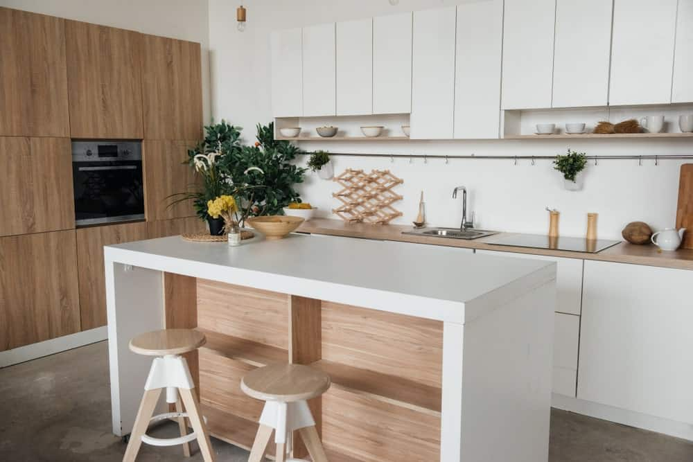 A classy Scandinavian-Style kitchen offers a small center island providing space for a breakfast bar for two. The center island also provides additional space for shelves.