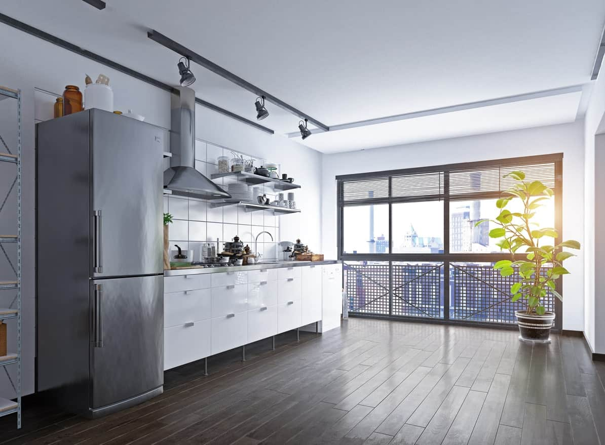 A spacious Scandinavian kitchen with a hardwood flooring and an indoor plant set on the corner. The gray fridge matches the kitchen shelving and countertop.