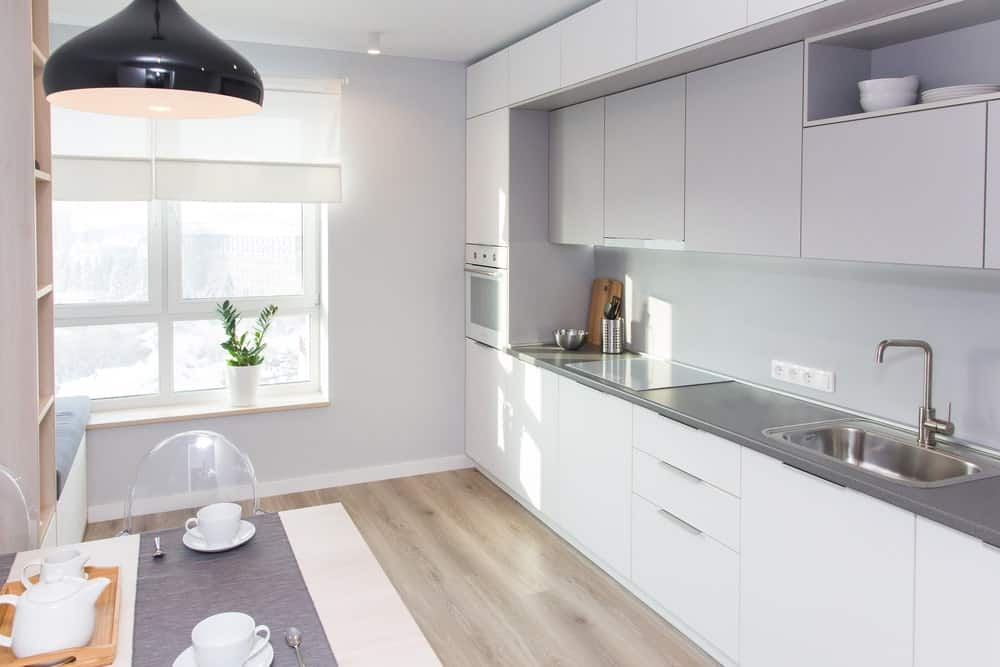 This Scandinavian kitchen features a hardwood flooring, white cabinetry and counters with a dining table set on the middle.
