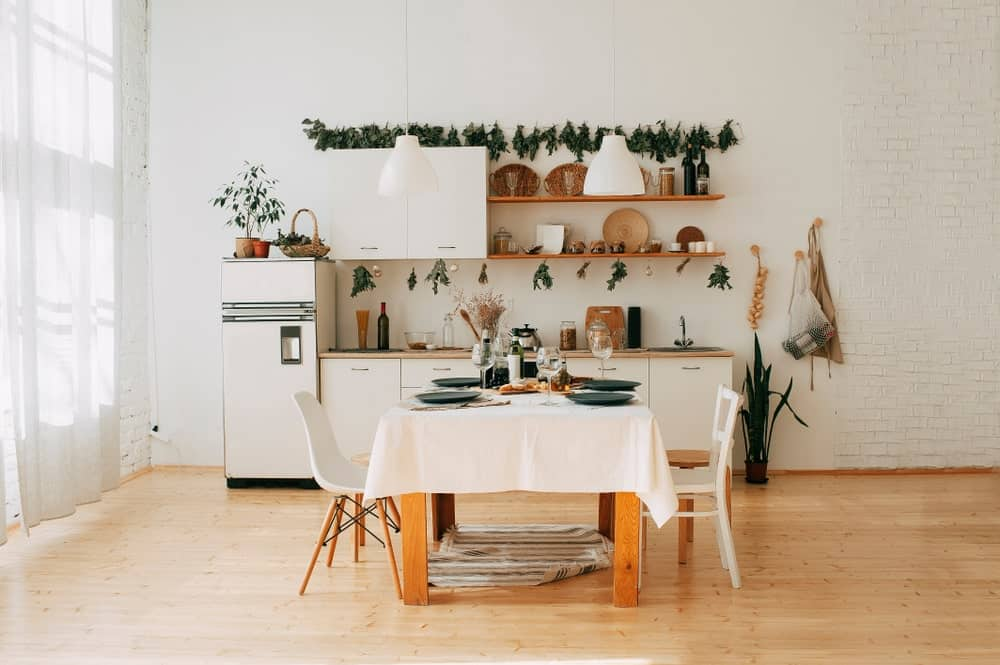A spacious Scandinavian kitchen style featuring hardwood flooring and rustic shelves and table. The white walls, cabinetry and counters look absolutely beautiful together with the green shade.