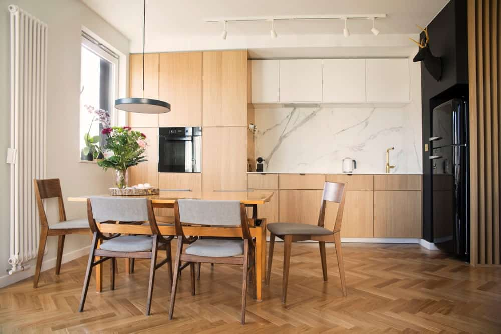 This Scandinavian-Style kitchen boasts a herringbone style flooring matching the kitchen counter and dining table set. The marble backsplash looks absolutely stunning along with the black fridge on the corner.