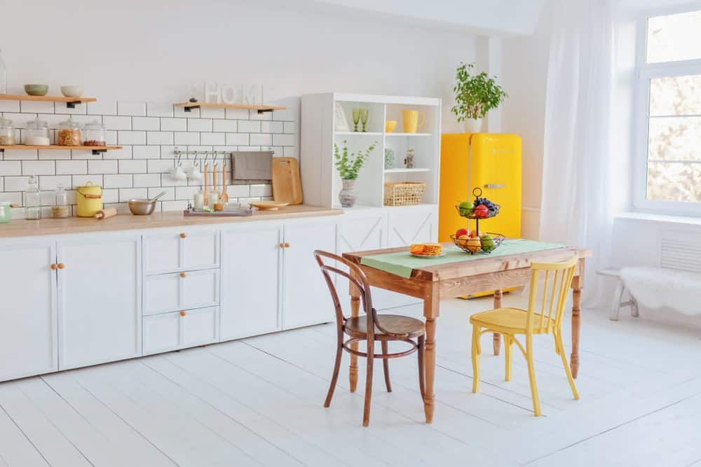 A spacious Scandinavian kitchen with yellow fridge and brown shelves and countertop along with a wooden dining table set on the white hardwood flooring.