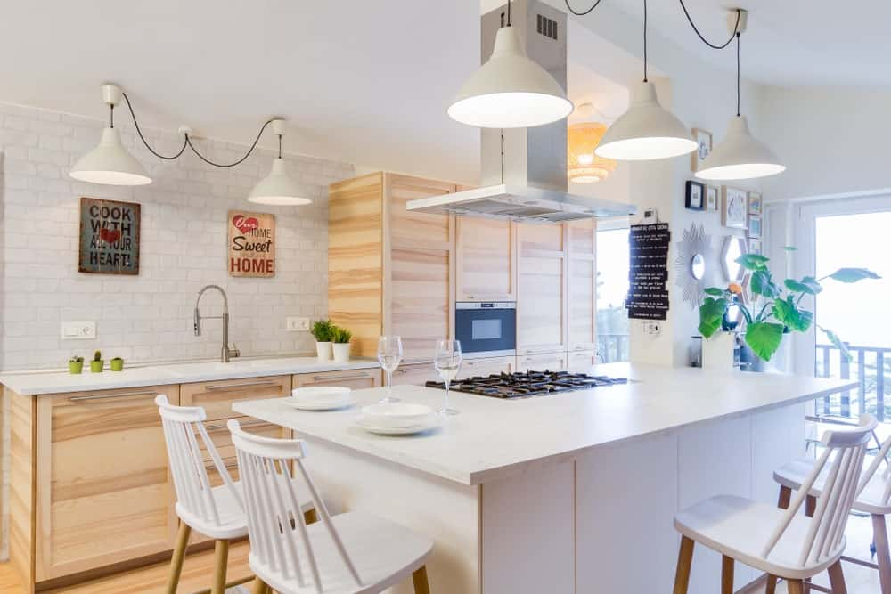 This Scandinavian-Style kitchen boasts a large white center island providing space for a breakfast bar lighted by white pendant lights.