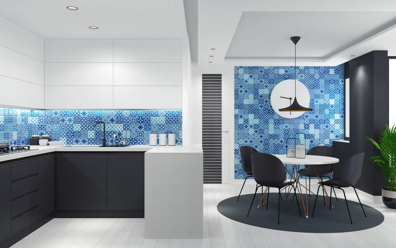 This Scandinavian kitchen boasts a very stylish blue wall and backsplash. The matte black finished kitchen counters and dining table seats on top of the matching rug look stunningly beautiful.