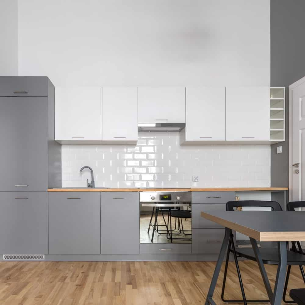 A modish Scandinavian-Style kitchen boasting gray counters, walls and a dining table set on a hardwood flooring.
