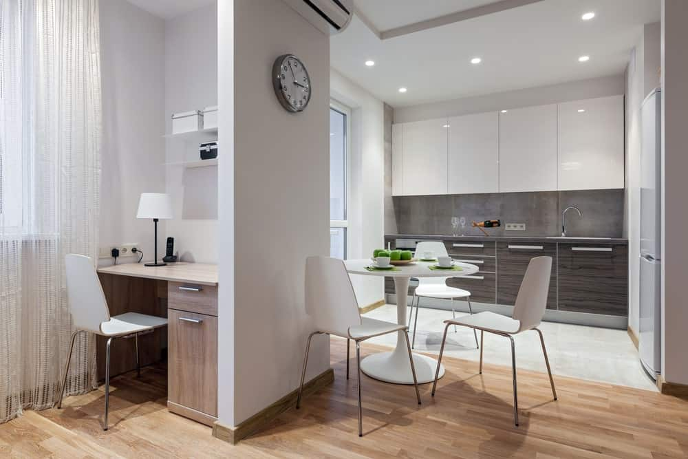 A modish Scandinavian-Style kitchen featuring a small dining nook set and a small work desk on the corner.