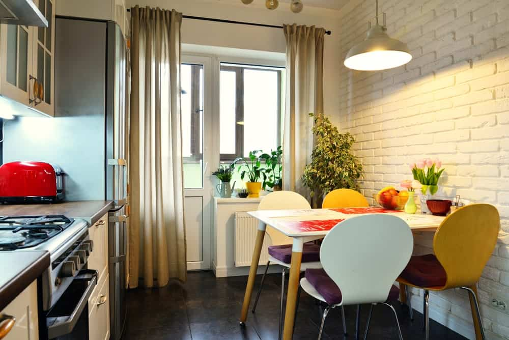 Small Scandinavian kitchen featuring dark brown tiles flooring and a dining nook for four lighted by a pendant light.