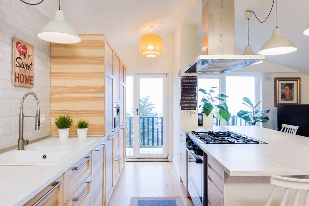 This Scandinavian-Style kitchen boasts the combination of white countertops and wooden cabinetry and kitchen counters. The warm white pendant lighting looks perfect with the kitchen's style.