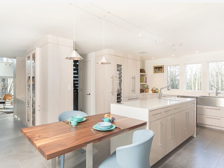 A large Scandinavian style kitchen boasting a thick plank dining nook connected to the white center island with a smooth countertop. The gray tiles flooring looks classy.