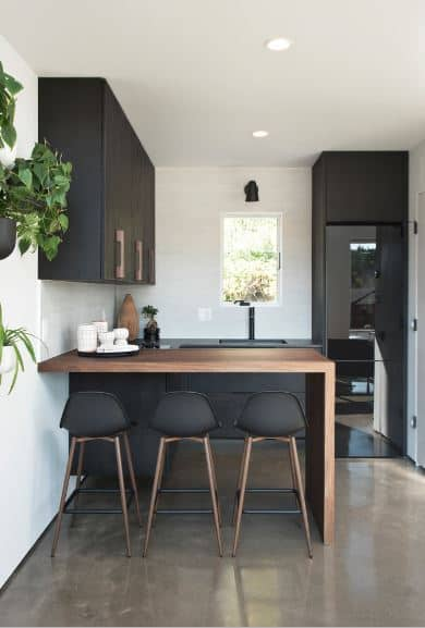 The balance between the elements of the wooden hues and black sleekness is the emphasis of this Scandinavian-Style kitchen. The sleek black fridge blends well with the black sink area and cabinets that are mounted on the white walls as well as the black stools.