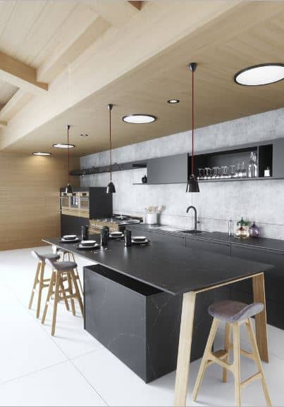 The wooden ceiling and wooden wall are contrasted by the dark elements of the kitchen peninsula and kitchen islands that have dark marble countertops. The peninsula is given a light gray backsplash contrasted by the black wooden hanging structure with built-in cabinets and shelves.