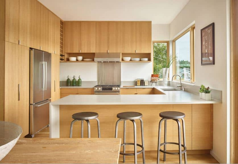 The modern metallic fridge is embedded into a large wooden structure that dominates one of the walls. It has built-in cabinets that extend to the hanging cabinets of the next wall over the U-shaped peninsula that has white countertops and wooden body.